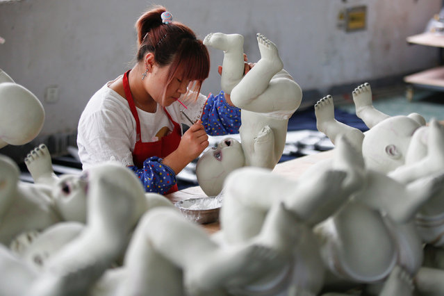 A worker paints a doll at Jinhua Partytime Latex Art and Crafts Factory in Jinhua, Zhejiang Province, China, May 25, 2016. (Photo by Aly Song/Reuters)