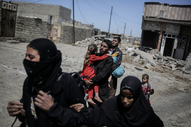 Mosul residents flee their homes as Iraqi forces battle the Islamic State group in a street to street fight in west Mosul, Monday, April 24, 2017. (Photo by Bram Janssen/AP Photo)