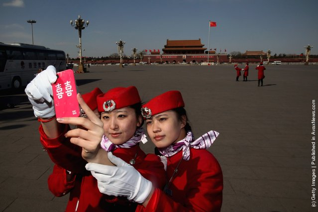 Hostesses pose for photos in windy during the third plenary meeting of the 11th National Committee of the Chinese People's Political Consultative Conference (CPPCC) at The Great Hall Of The People