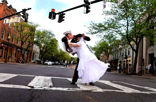 Marine Cpl. Nicholas Kulla kisses his wife, Jennifer, on their wedding day in Skaneateles, New York, Saturday, May 28, 2016. The kiss brought cheers and a few Semper Fi's from passersby in the village. The two married this memorial Day weekend two years after meeting in San Diego where Kulla was stationed. Kulla is now stationed in North Carolina hoping to soon earn the rank of sergeant. (Photo by Kevin Rivoli/AP Photo)