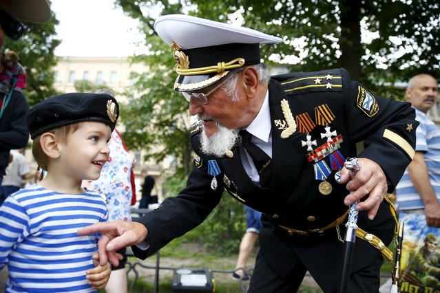 A Russian navy veteran talks to a boy during celebrations for Navy Day in St. Petersburg, Russia, July 26, 2015. (Photo by Reuters/Stringer)