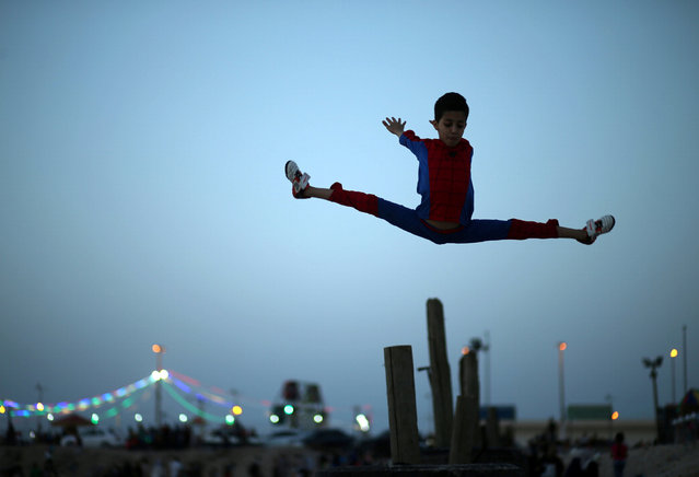 """Palestinian boy Mohamad al-Sheikh, 12, who is nicknamed """"Spiderman"""" and hopes to break the Guinness world records with his bizarre feats of contortion, demonstrates acrobatics skills on a beach in Gaza City June 2, 2016. (Photo by Mohammed Salem/Reuters)"""