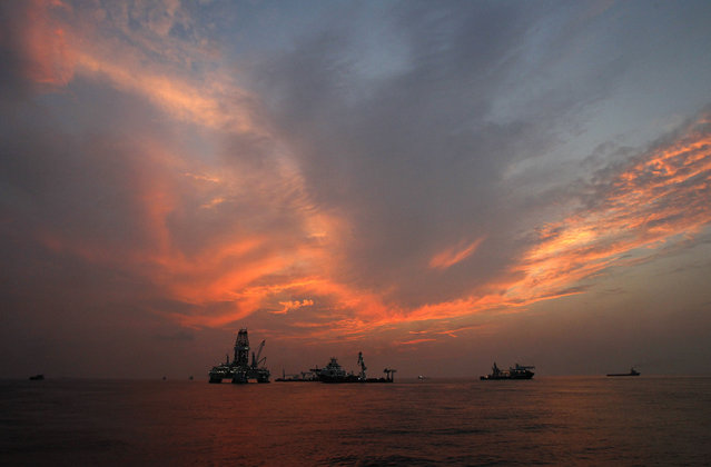 This Saturday, September 4, 2010 file photo shows vessels assisting in the drilling of the Deepwater Horizon relief well on the Gulf of Mexico near the coast of Louisiana at sunset. (Photo by Patrick Semansky/AP Photo)