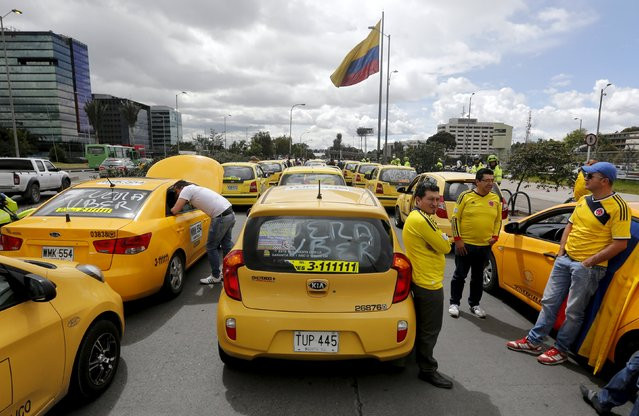 Cab drivers block an avenue to protest against the Uber ride sharing service in Bogota July 29, 2015. (Photo by John Vizcaino/Reuters)