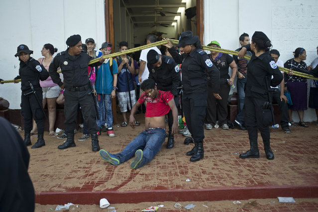 An intoxicated man is dragged away by a policeman out of the area where promise keepers dance with a Managua's patron saint, Santo Domingo de Guzman, in Managua, Nicaragua, Saturday, August 1, 2015. Promise keepers dance inside the church along with the image of the saint as a way to pay a promise made for a perceived miracle or answer to their prayers. (Photo by Esteban Felix/AP Photo)
