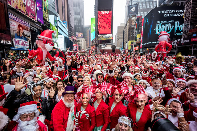 Revellers gather for the start of the Annual SantaCon Bar Crawl at Father Duffy Square, a section of Times Square, on December 14, 2019, in New York City. SantCon is an event where people make donations to charitable causes and dress up as a Christmas character and visit bars around the city. (Photo by Steven Ferdman/Getty Images)
