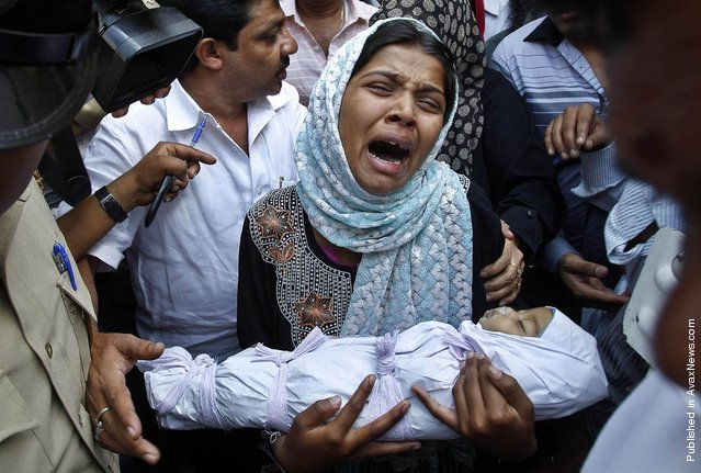 Reshma Bano wails as she holds the body of her 3-month-old daughter Neha Afreen outside a hospital morgue in Bangalore, India