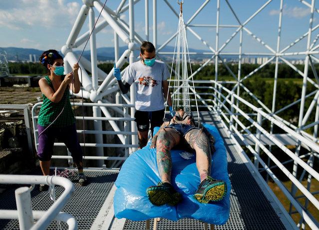 Professional body artist Dino Helvida (C), 27, and his girlfriend Zorana Unkovic (L), 27, prepare Kaitlin, 28, from the United States for body suspension in Zagreb, Croatia June 7, 2016. (Photo by Antonio Bronic/Reuters)