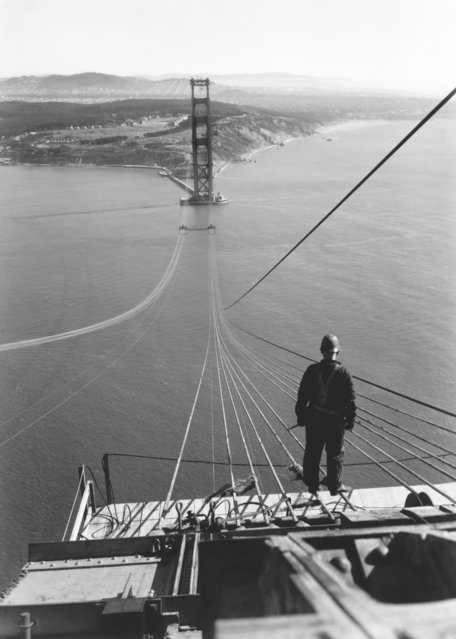 A man standing on the first cables during the construction of the Golden Gate Bridge with the Presidio and San Francisco in the background, San Francisco, California, 1935. (Photo by Underwood Archives/Getty Images)
