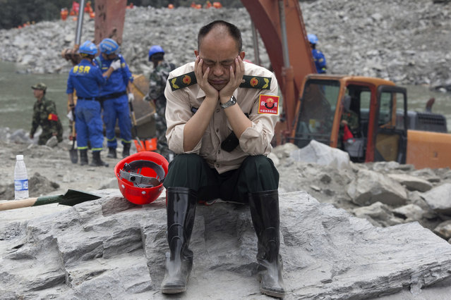 A rescue worker takes a nap at the site of a landslide in Xinmo village in Maoxian County in southwestern China's Sichuan Province, Sunday, June 25, 2017. (Photo by Ng Han Guan/AP Photo)