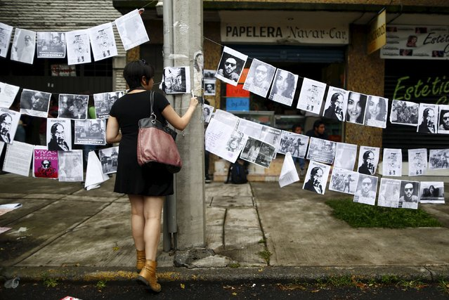 A demonstrator hangs pictures during a demonstration against the murder of photojournalist Ruben Espinosa and four other women outside the building where the bodies were found in Mexico City, August 5, 2015. Espinosa, a prominent Mexican news photographer was among five people found dead in a middle-class neighborhood of the capital on July 31, 2015. (Photo by Edgard Garrido/Reuters)