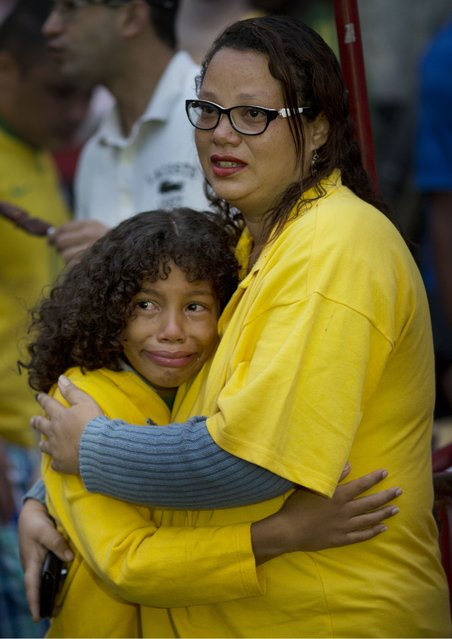 Brazil soccer fans embrace as they watch their team lose to Germany via a live telecast of the World Cup semifinal game in Sao Paulo, Brazil, Tuesday, July 8, 2014. (Photo by Rodrigo Abd/AP Photo)