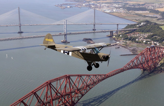 Jim McTaggart takes his 1940 Piper Cub for a practice flight over the Forth rail bridge, the Forth road bridge and the new Queensferry crossing ahead of the aircraft's appearance at Scotland's National Airshow in Queensferry, Scotland on July 19, 2017. (Photo by Andrew Milligan/PA Wire)