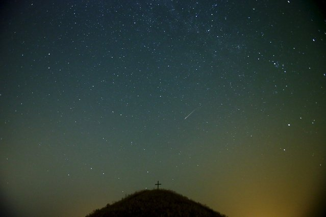 A meteor streaks across the sky over Leeberg hill during the Perseid meteor shower near Grossmugl in the early morning of August 13, 2015. (Photo by Heinz-Peter Bader/Reuters)