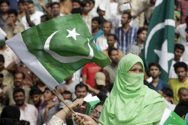 A woman waves Pakistan's national flag during a ceremony to mark the country's 69th Independence Day at the Wagah border near Lahore, Pakistan August 14, 2015. (Photo by Mohsin Raza/Reuters)