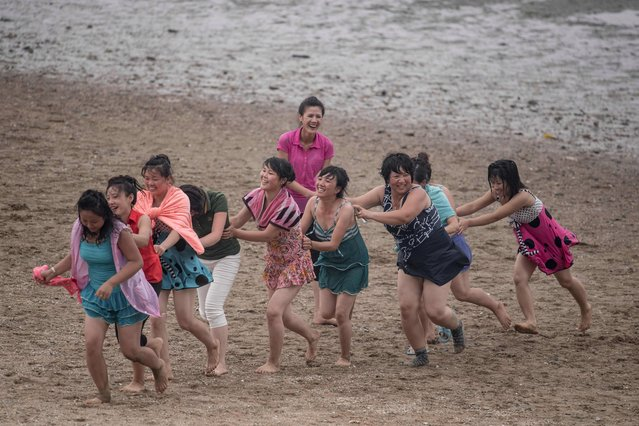 A photo taken on July 22, 2017 shows a group of women playing a game at the West Sea Barrage beach outside the coastal city of Nampo, southwest of Pyongyang. (Photo by Ed Jones/AFP Photo)