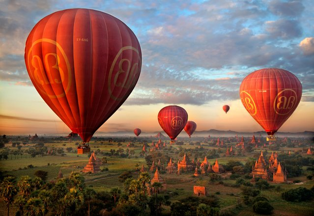 """The fantastic landscape of Bagan in Myanmar features hundreds of temples and pagodas as far as the eye can see. Experiencing this sight at dawn from the basket of a hot air balloon will remain engraved in my memory for ever. Mick Ryan, judge – What a magical photograph and place. The Buddhist temples and pagodas fill the plains of Bagan in Myanmar at sunrise… the golden hour providing beautiful light to illuminate the retrogression of the temples and balloons toward a misty, mountainous distance. An excellent, exotic photograph that makes you want to book a flight"". (Photo by Alastair Swan/The Guardian)"
