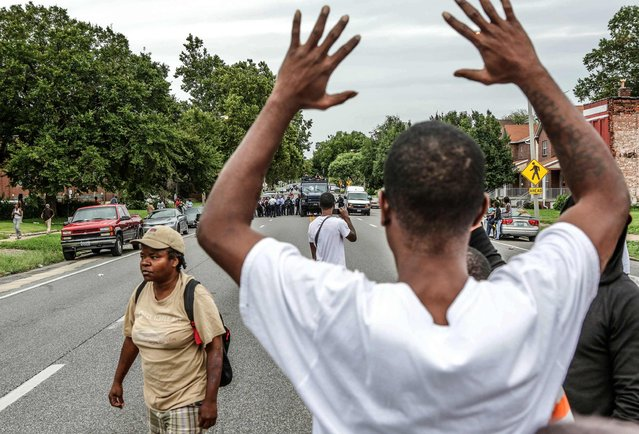 Protestors hold their hands up as police approach them on Page Ave. after a shooting incident in St. Louis, Missouri August 19, 2015. (Photo by Lawrence Bryant/Reuters)