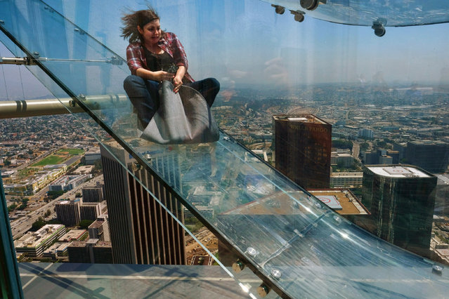 A member of the media rides down a glass slide during a media preview at the U.S. Bank Tower building in downtown Los Angeles on Thursday, June 23, 2016. Starting this weekend, thrill-seekers can begin taking the Skyslide, a 1,000 feet high slide, perched on the outside of the tallest skyscraper west of the Mississippi. (Photo by Richard Vogel/AP Photo)