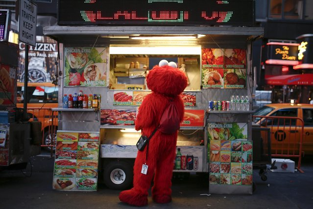 Jorge, an immigrant from Mexico, and dressed as the Sesame Street character Elmo, buys food from a street food cart in Times Square, New York July 30, 2014. (Photo by Eduardo Munoz/Reuters)