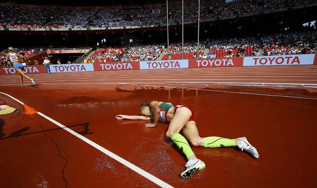 Sviatlana Kudzelich of Belarus falls in the women's 3,000 metres steeplechase heat during the 15th IAAF World Championships at the National Stadium in Beijing, China August 24, 2015. (Photo by Kai Pfaffenbach/Reuters)