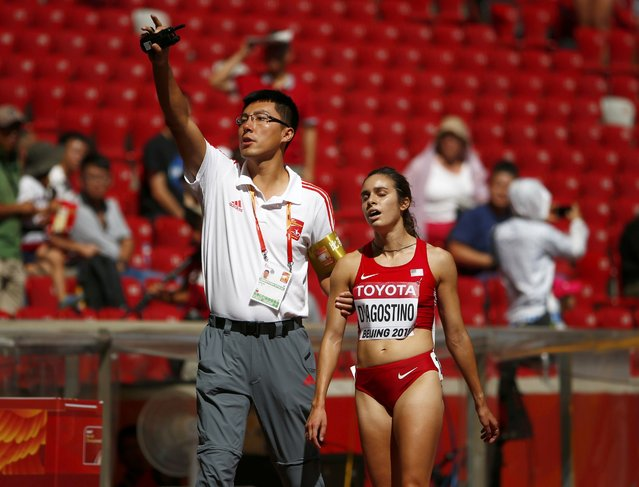 An official calls for assistance for Abbey D'gostino of the U.S after the women's 5,000 metres heats during the 15th IAAF World Championships at the National Stadium in Beijing, China August 27, 2015. (Photo by David Gray/Reuters)