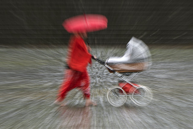 In this zoomed and long time exposure picture a woman walks with her buggy during heavy rain in Erfurt, Germany, Thursday, June 29, 2017. Weather forecasts predict changeable weather conditions in Germany for the upcoming day. (Photo by Jens Meyer/AP Photo)