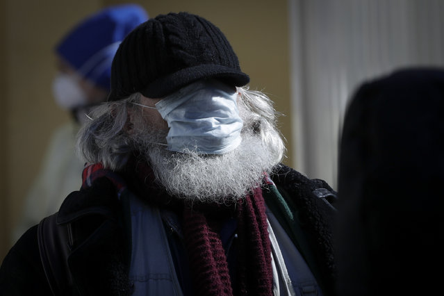 A homeless man wearing face masks to protect against coronavirus, waits to receive basic medial help from members of a group of volunteer doctors of the Dom Druzei (Home of Friends) NGO in Moscow, Russia, Wednesday, April 1, 2020. As Moscow goes into lockdown amid the coronavirus pandemic, thousands of homeless people have trouble receiving food, water and shelter as Russia's capital closes non-essential businesses, cafes and parks. (Photo by Pavel Golovkin/AP Photo)