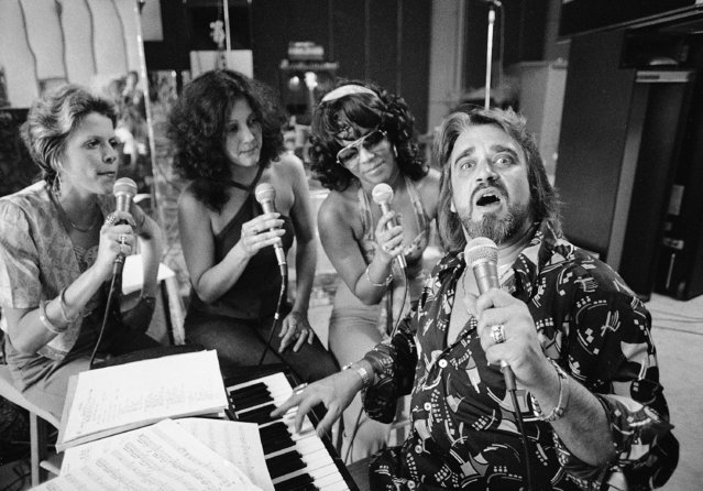 """Wolfman Jack, famed radio disc jockey, rehearses at this Beverly Hills home for a musical show he has produced to promote radio, June 10, 1975. In the show """"I Saw Radio"""", Jack sings, dances, plays the piano and raps with the audience. Working with him are Irene Cathaway, center, and Gwen Owens. Woman at far left unidentified. (Photo by Wally Fong/AP Photo)"""