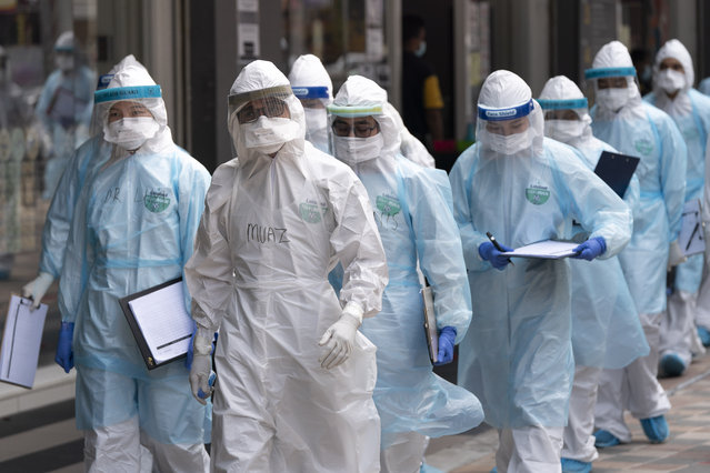 Medical workers in protective suits entering a building under lockdown in downtown Kuala Lumpur, Malaysia, on Tuesday, April 7, 2020. The Malaysian government issued a restricted movement order to the public to help curb the spread of the new coronavirus. (Photo by Vincent Thian/AP Photo)