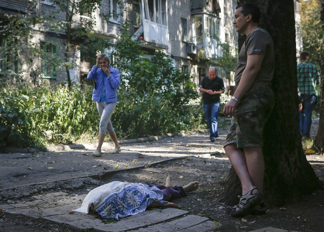 Local residents walk past as a man stands near the body of a victim killed by what locals say was recent shelling by Ukrainian forces in Donetsk August 23, 2014. (Photo by Maxim Shemetov/Reuters)