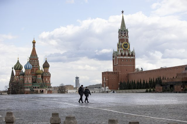 Two police officers patrol an almost empty Red Square, with St. Basil's Cathedral, center, and Spasskaya Tower in Moscow, Russia, Monday, April 20, 2020. Officials in Moscow and other regions have ordered most people except those working in essential sectors to stay home through April 30. Residents are only allowed to shop at nearby food stores and pharmacies, walk their dogs and remove trash. (Photo by Alexander Zemlianichenko/AP Photo)