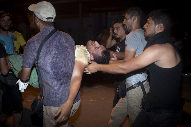 Migrants carry an injured migrant during scuffles with police as they tried to embark a passenger ship heading to Athens without a ticket, at the port of Mytilene on the Greek island of Lesbos, September 5, 2015. (Photo by Dimitris Michalakis/Reuters)