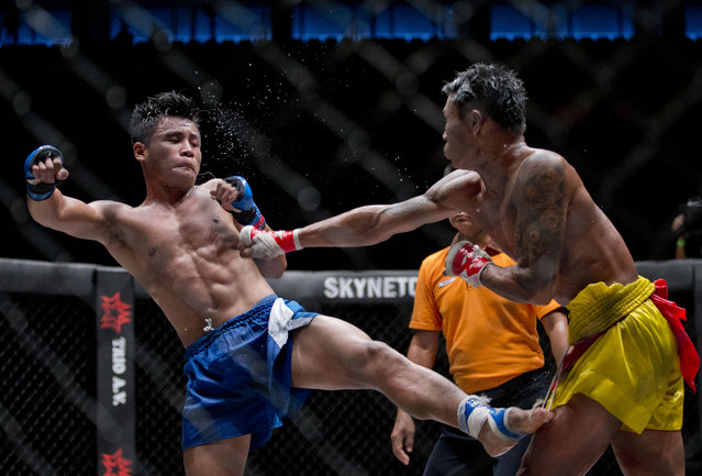 """In this Saturday, July 18, 2015, photo, fighters exhibit lethwei –a Myanmar traditional martial art which practices a rough form of kickboxing – at a mixed-martial-arts """"One Championship"""" event broadcast globally on cable television networks, in Yangon, Myanmar. Fighters could receive $1,000 for each fight, according to coach Myint Zaw who runs a street side traditional fighters' club he started 15 years ago. (Photo by Gemunu Amarasinghe/AP Photo)"""