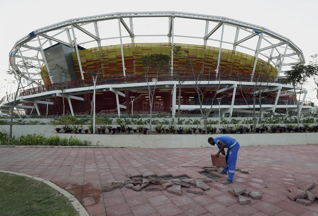 A worker installs pavers outside the Olympic Tennis Center as preparations continue for the 2016 Summer games at Olympic Park in Rio de Janeiro, Brazil, Monday, August 1, 2016. (Photo by Charlie Riedel/AP Photo)