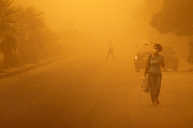 A woman wearing a facemark walks through a sandstorm in Homs, Syria September 7, 2015. (Photo by Omar Sanadiki/Reuters)