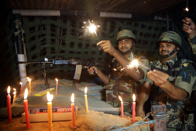 Indian Border Security Force (BSF) soldiers burn firecrackers in their bunker during Diwali festival celebrations at Akhnoor, about 35 km from Jammu, the winter capital of Kashmir, India, 18 October 2017. Diwali is known as the festival of lights and symbolizes the victory of good over evil and commemorates the Hindu God Lord Rama's return to his kingdom Ayodhya. The festival will be celebrated on 19 October. (Photo by Jaipal Singh/EPA/EFE)
