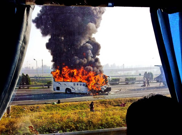 A tourist bus is engulfed in flames on an expressway near Tianjin, China, on Oktober 1, 2012. 5 Germans and a Chinese citizen were killed when the bus burst into flames after hitting the back truck. (Photo by Xinhua)