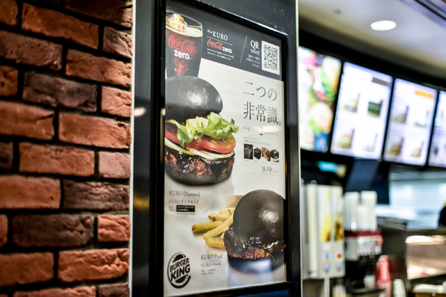 An advertising poster touting the new black hamburger is seen at a Burger King restaurant on September 18, 2014 in Tokyo, Japan. (Photo by Keith Tsuji/Getty Images)