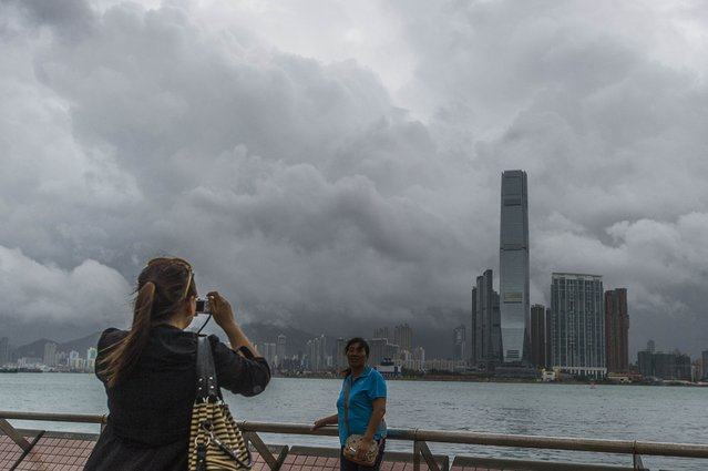 Chinese tourists take pictures in front of the Kowloon skyline during a thunderstorm in Hong Kong caused by Typhoon Kalmaegi on September 16, 2014. Hong Kong was shuttered on September 16 as a powerful typhoon swept past the city, bringing strong winds and rain that caused flight disruptions and forced the closure of the stock market and container ports. (Photo by Xaume Olleros/AFP Photo)