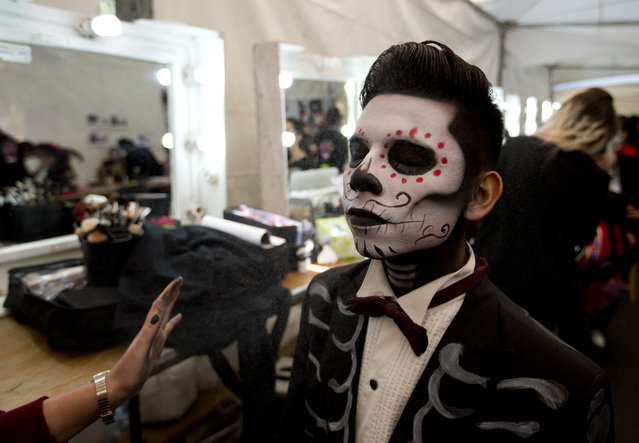 "A young man has his make up applied as he prepares for the start of a Day of the Dead parade to begin along Mexico City's main Reforma Avenue, Saturday, October 28, 2017. Mexico's capital is holding its Day of the Dead parade, an idea actually born out of the imagination of a scriptwriter for the James Bond movie ""Spectre"". (Photo by Eduardo Verdugo/AP Photo)"
