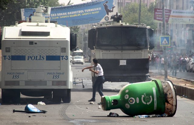A protester throws stones at police vehicles in the Kurdish dominated southeastern city of Diyarbakir, Turkey, September 13, 2015. (Photo by Sertac Kayar/Reuters)