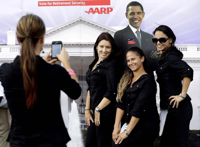 Workers later pose for a photo with the cutout of President  Obama. (Photo by Eric Gay/Associated Press)