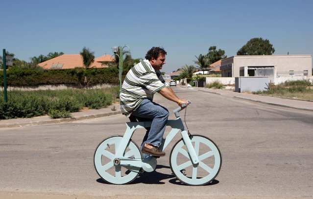 A bicycle made almost entirely of cardboard has the potential to change transportation habits from the world's most congested cities to the poorest reaches of Africa, its Israeli inventor says. Izhar Gafni, 50, is an expert in designing automated mass-production lines. He is an amateur cycling enthusiast who for years toyed with an idea of making a bicycle from cardboard. He told Reuters during a recent demonstration that after much trial and error, his latest prototype has now proven itself and mass production will begin in a few months. (Photo by Baz Ratner/Reuters)