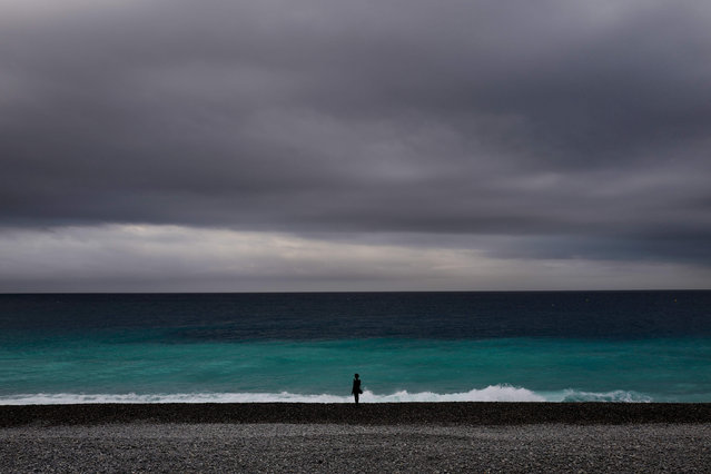 A woman looks at the Mediterranean sea from the beach of French Riviera city of Nice, southern France, on May 13, 2020, as a partial lifting of restrictions introduced two months ago to fight the spread of the Covid-19 pandemic caused by the novel coronavirus comes into effect. (Photo by Valery Hache/AFP Photo)