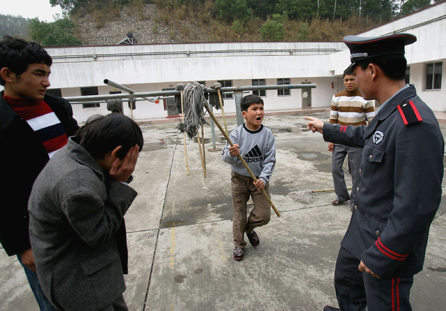 A Chinese kid moves to beat a security guard at an assistance center February 23, 2005 in Shenzhen, Guangdong Province, China. (Photo by Cancan Chu/Getty Images)