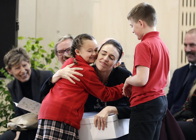 New Zealand Prime Minister Jacinda Ardern embraces a pupil during the opening ceremony for Redcliffs School in Christchurch, New Zealand, Thursday, June 25, 2020. The school was rebuilt following earthquakes almost nine years to the day forced pupils and staff from the site. (Photo by Mark Baker/AP Photo)