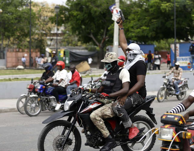 Armed off-duty police officers ride motorcycles and fire their weapons in the air during a protest over pay and working conditions, in Port-au-Prince, Haiti, Sunday, February 23, 2020. (Photo by Dieu Nalio Chery/AP Photo)