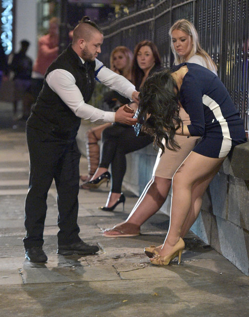 A bouncer rushes to the aid of a woman as she throws up. Mayhem hits the streets of Newcastle, UK as clubbers out on the Toon have a little too much to drink as they enjoy the Bank Holiday on August 29, 2016. Photographs take last night show scantily-clad women passed out on the pavement, while boozed-up men were caught arguing with police. (Photo by XposurePhotos.com)