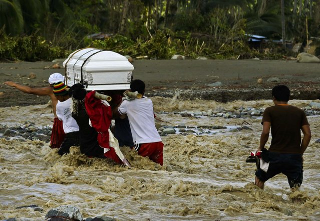 Relatives cross a river to bury their loved one, who died in a flash flood caused by Typhoon Bopha in New Bataan township in the southern Philippines, December 6, 2012. (Photo by Bullit Marquez/Associated Press)
